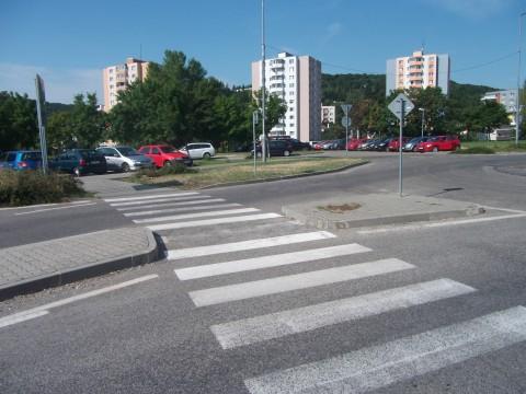 Priechod pre chodcov v Dúbravke. Stredovým ostrovčekom sa prechádza bez zapustených obrubníkov, či akýchkoľvek iných nerovností. Ide o súvislý asfaltový povrch. Podobne by mali byť riešené všetky križovania cestičiek pre cyklistov s vozovkou.
